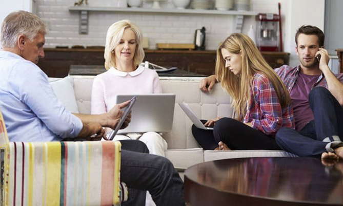 Family sitting together using electronic devices