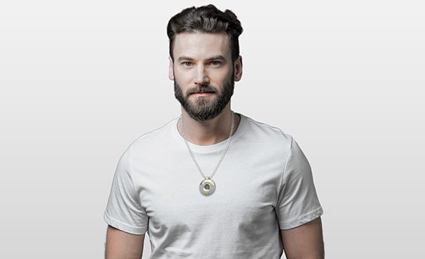 bearded man wearing a pendant with white background
