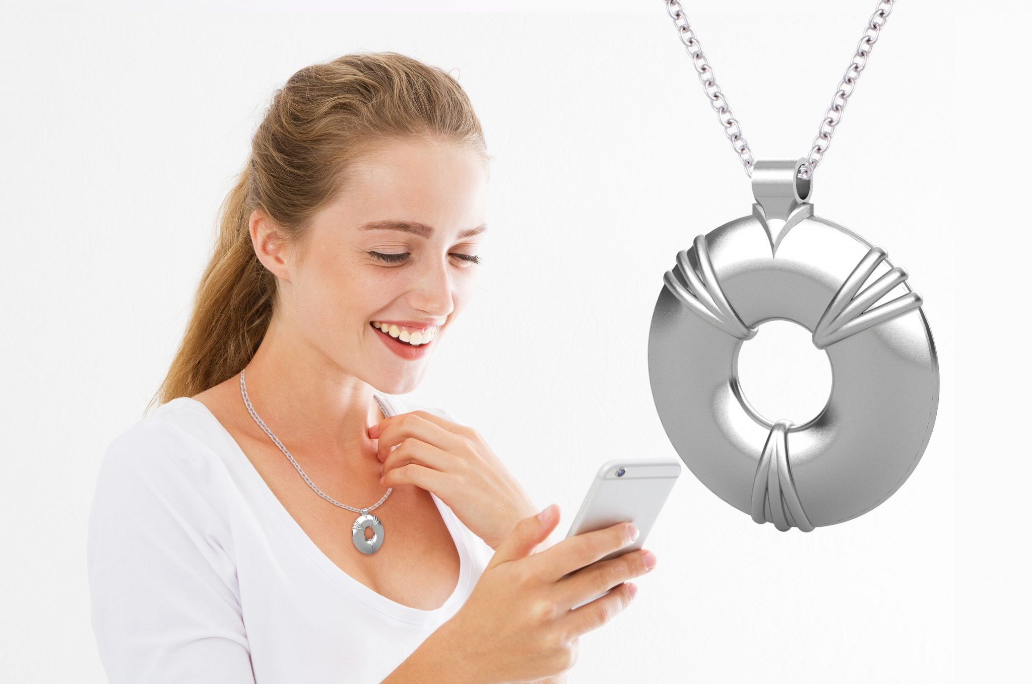 woman smiling on her phone holding her energy pendant